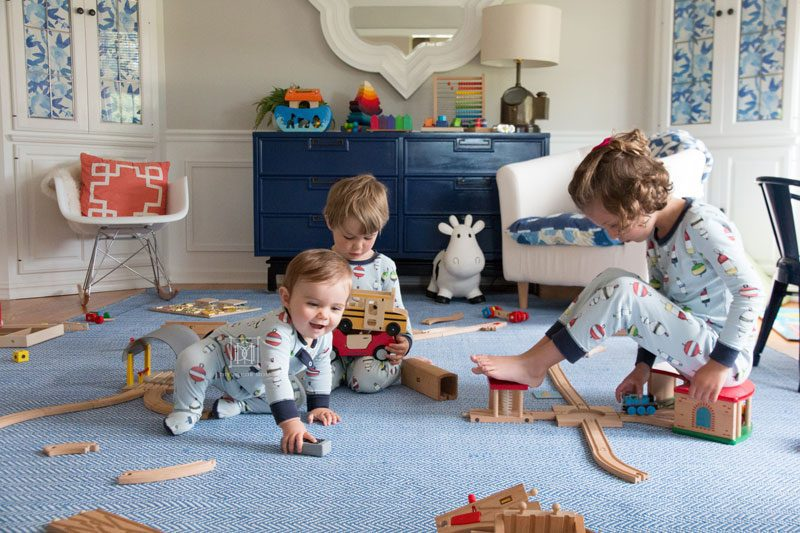 children playing in pajamas in playroom- indoor air quality concerns and how to improve it for families