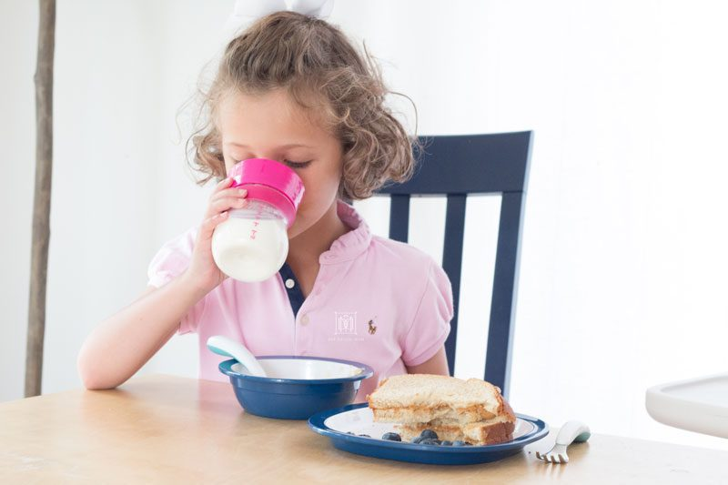 little girl drinking glass of milk from oxo transitions sippy cup