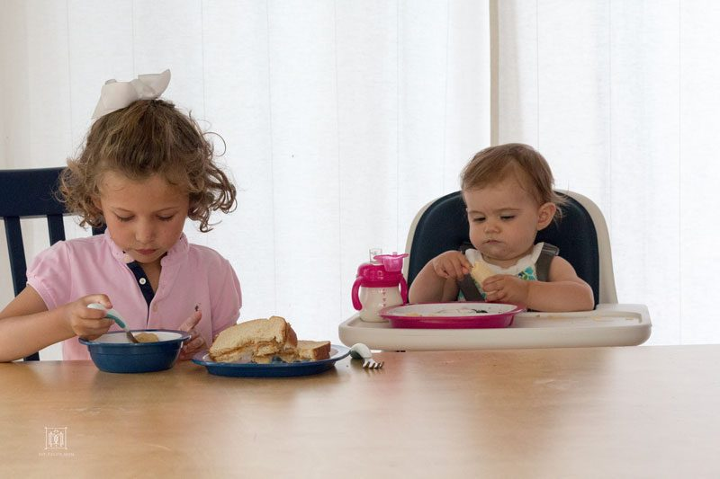 two sisters eating at dinner table