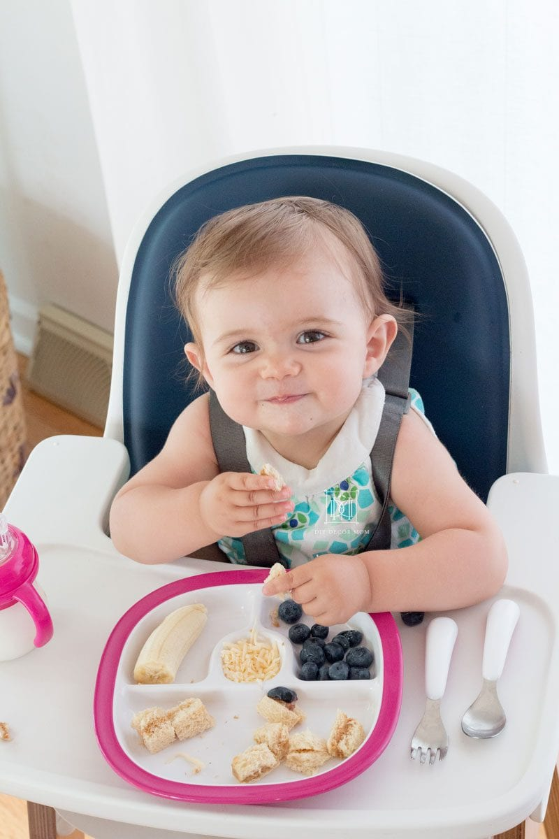 baby girl sitting in high chair with plate of baby led weaning food