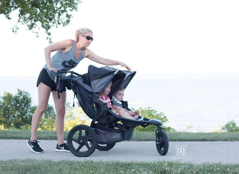 woman adjusting shade on double jogging stroller showing things to look for in best double jogging strollers