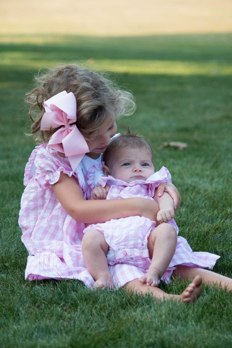 big sister holds newborn baby sister