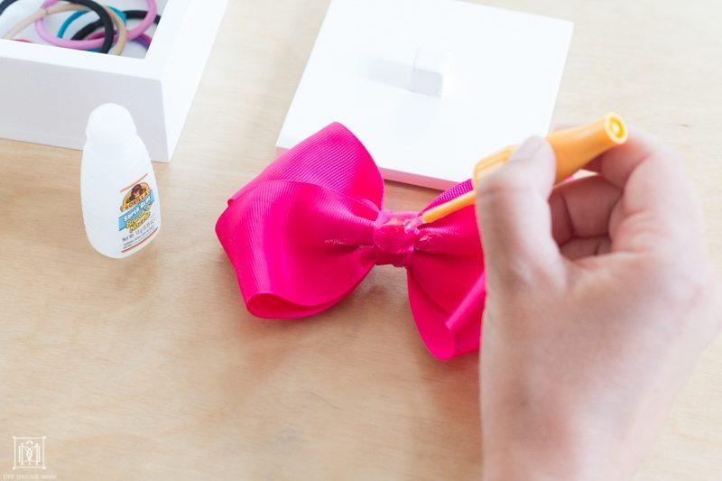 applying gorilla glue super glue brush & nozzle on white lacquer box with bow