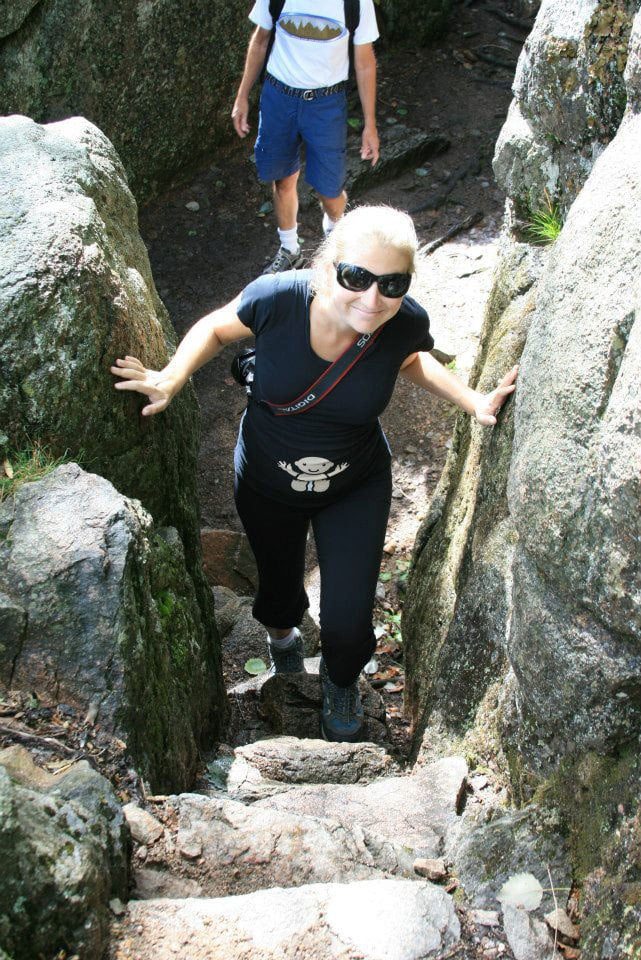 pregnant woman climbing mountain- babymoon a must do thing during your second trimester