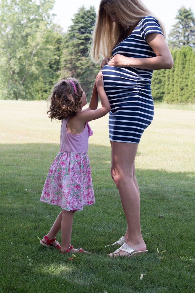 tips to help older siblings adjust to new baby sibling--pregnant mom and toddler daughter hug