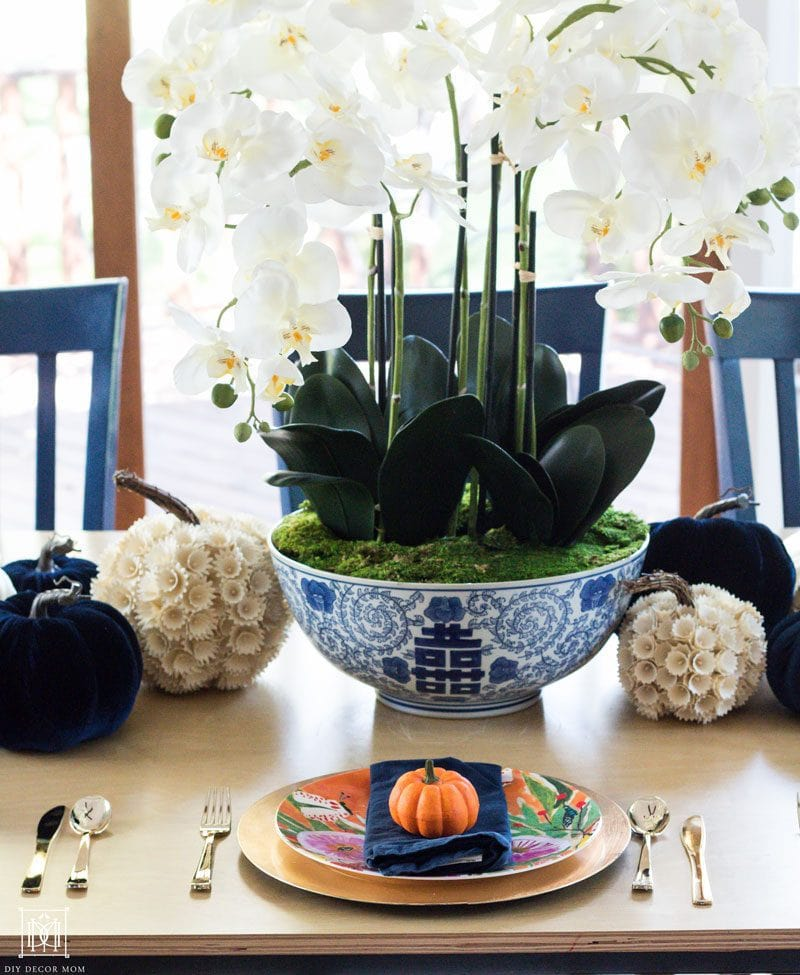 beautiful white orchids in blue and white ginger bowl with multicolored pumpkins of varying sizes including navy velvet pumpkins and white pumpkins