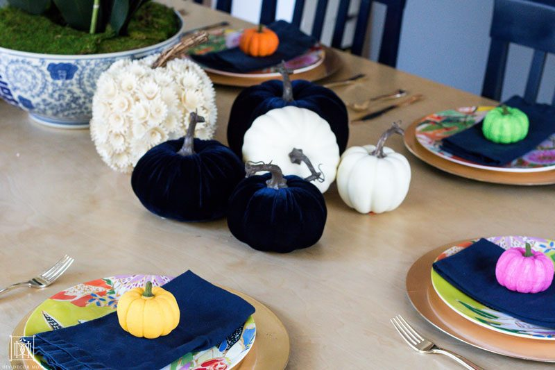 colorful pumpkins on a tablescape with blue napkins and gold chargers