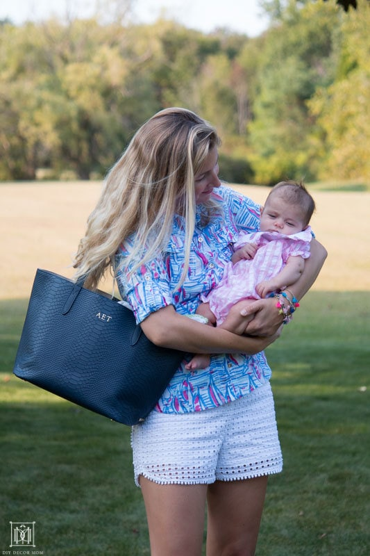 mom holding baby in backyard with blue diaper bag