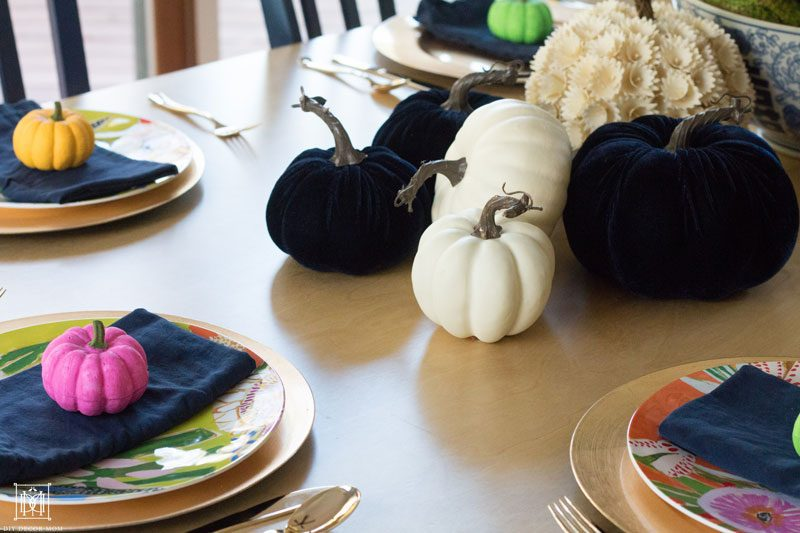 multicolored colorful pumpkin tablescape with navy velvet pumpkins and small colorful pink, yellow, green colored pumpkins