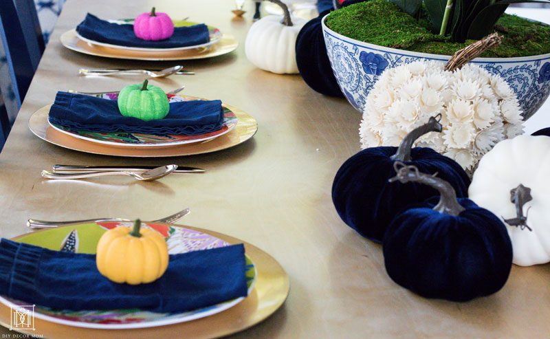tablesettings with gold chargers navy napkins and colorful pumpkins
