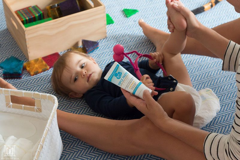 mom changing baby's diaper with triple paste ointment