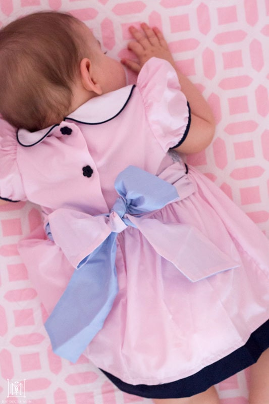 baby in a crib with pink dress