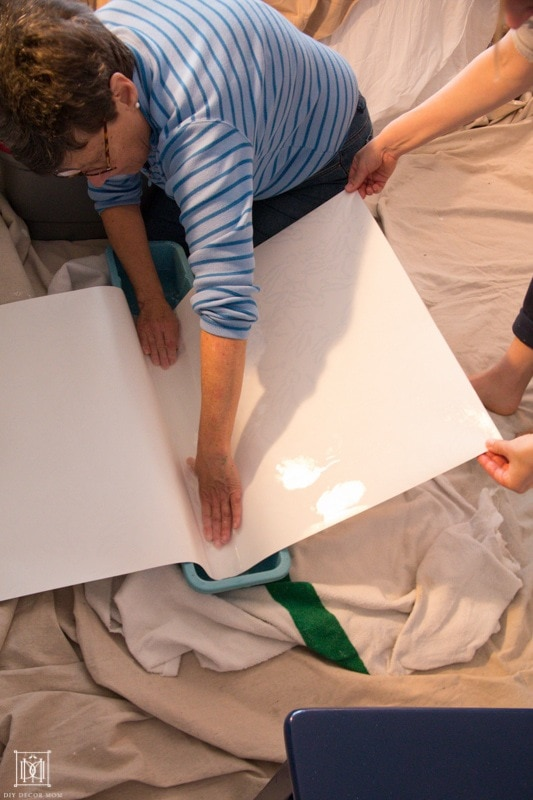 woman wetting the wallpaper to prepare for hanging