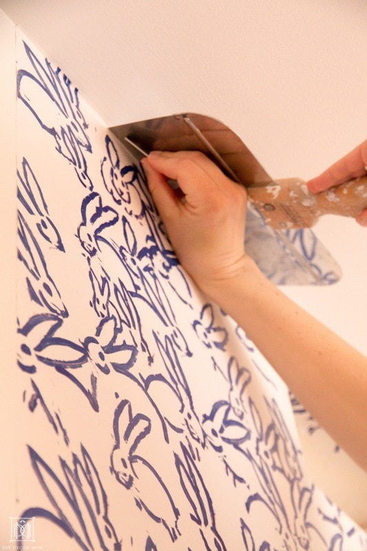 cut the excess wallpaper at the ceiling with a putty knife and a razor