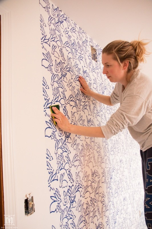 how to hang wallpaper: wmoan hanging wallpaper and wiping excess wallpaper adhesive off with wet sponge