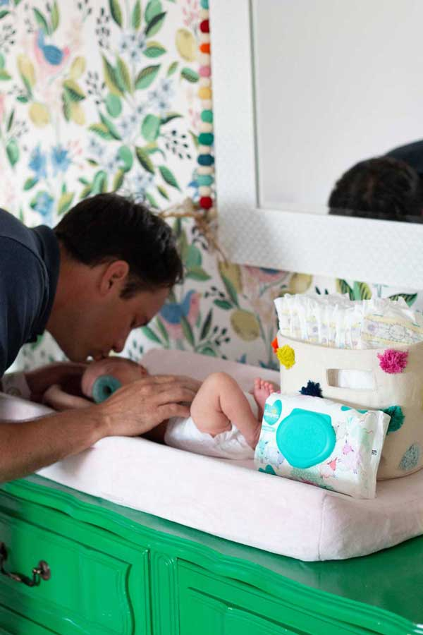 dad changing newborn diaper and kissing on head
