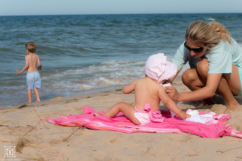 mom of three changing diapers at the beach