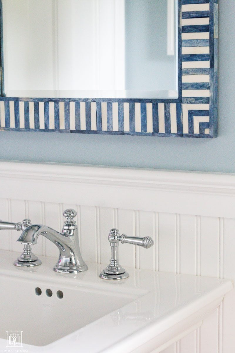 blue and white mirror on top of small pedestal sink in small bathroom with tips to make small bathrooms look big
