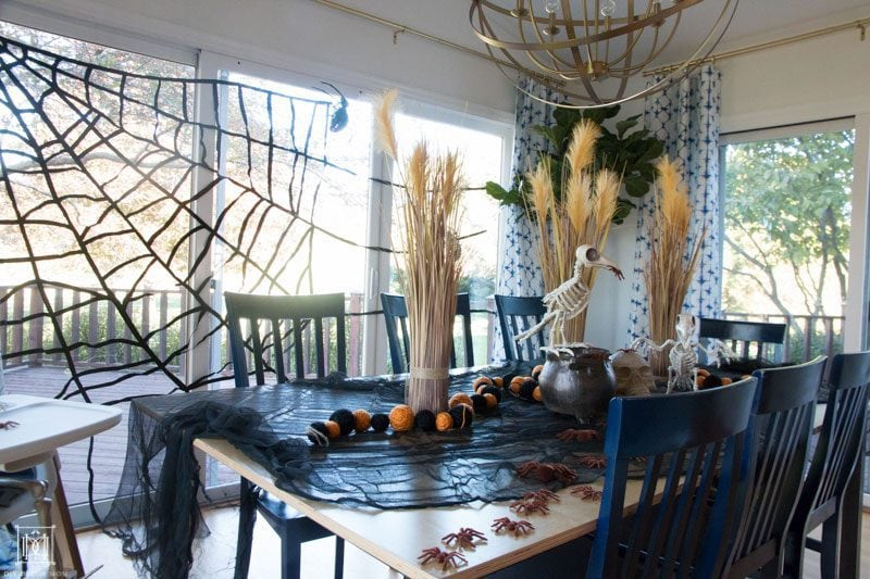 table with halloween decorations and spider web, skeletons, and skulls