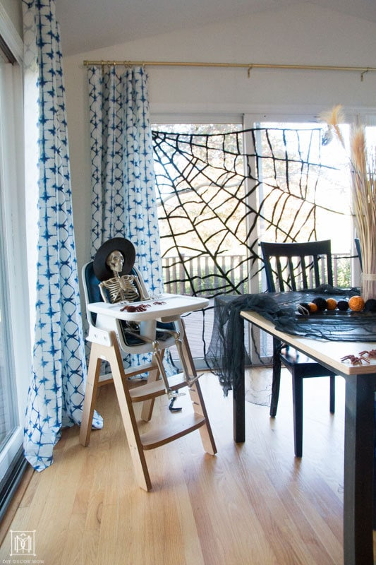 skeleton sitting in a high chair with giant spider web halloween table decor