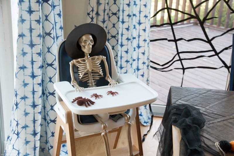 gold skeleton sitting in high chair with halloween table decor