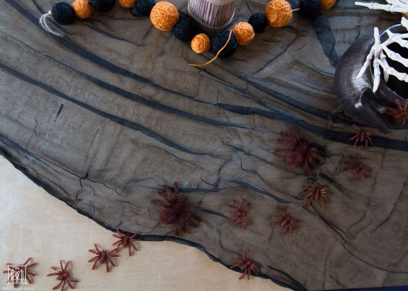 spiders on black tablecloth make spooky halloween decor ideas