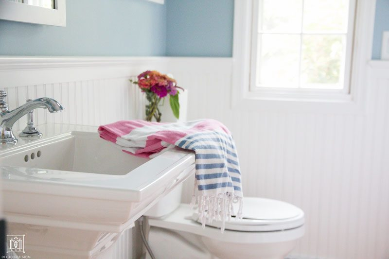 white pedestal sink and toilet in white beadboard small bathroom- 9 ways to make a bathroom seem bigger