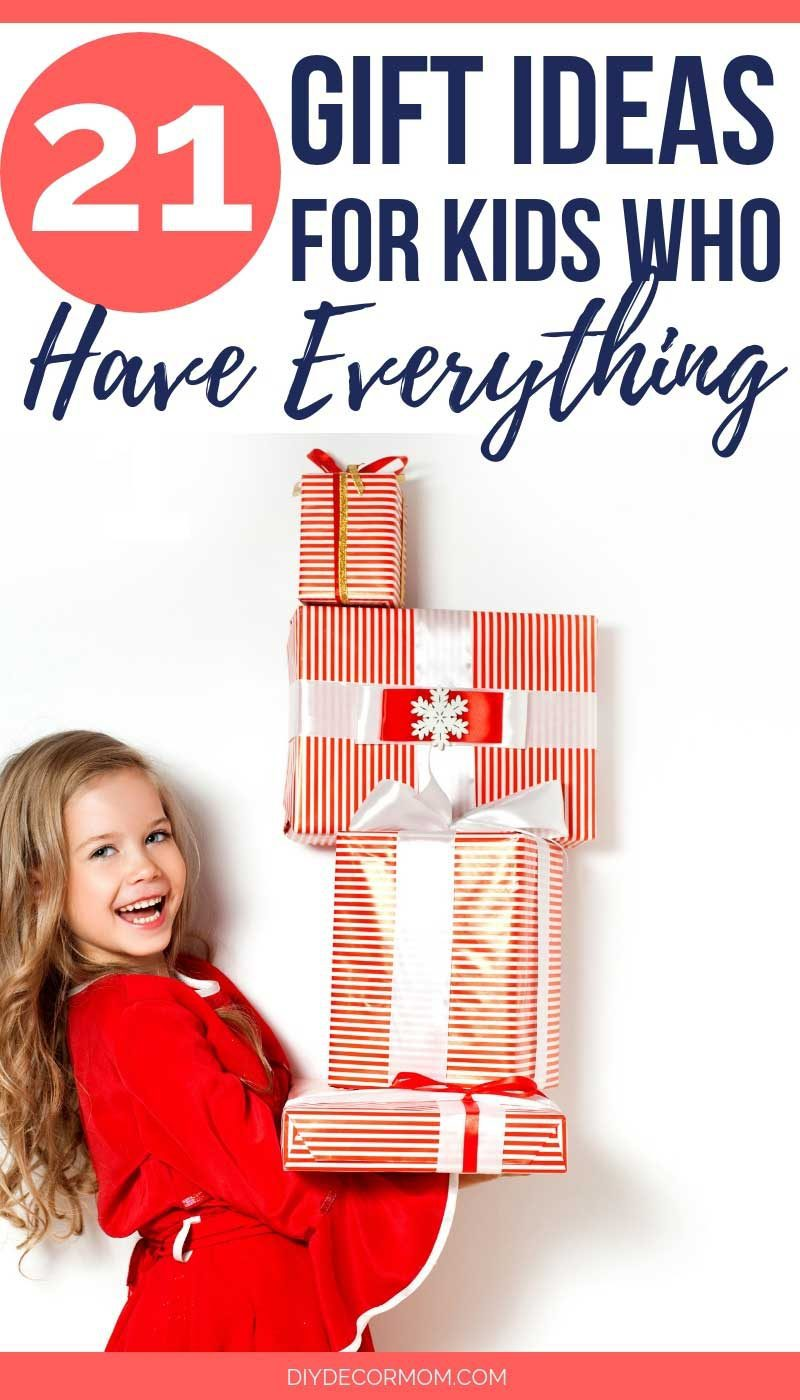girl holding christmas gifts- gift guide ideas for kids who have everything