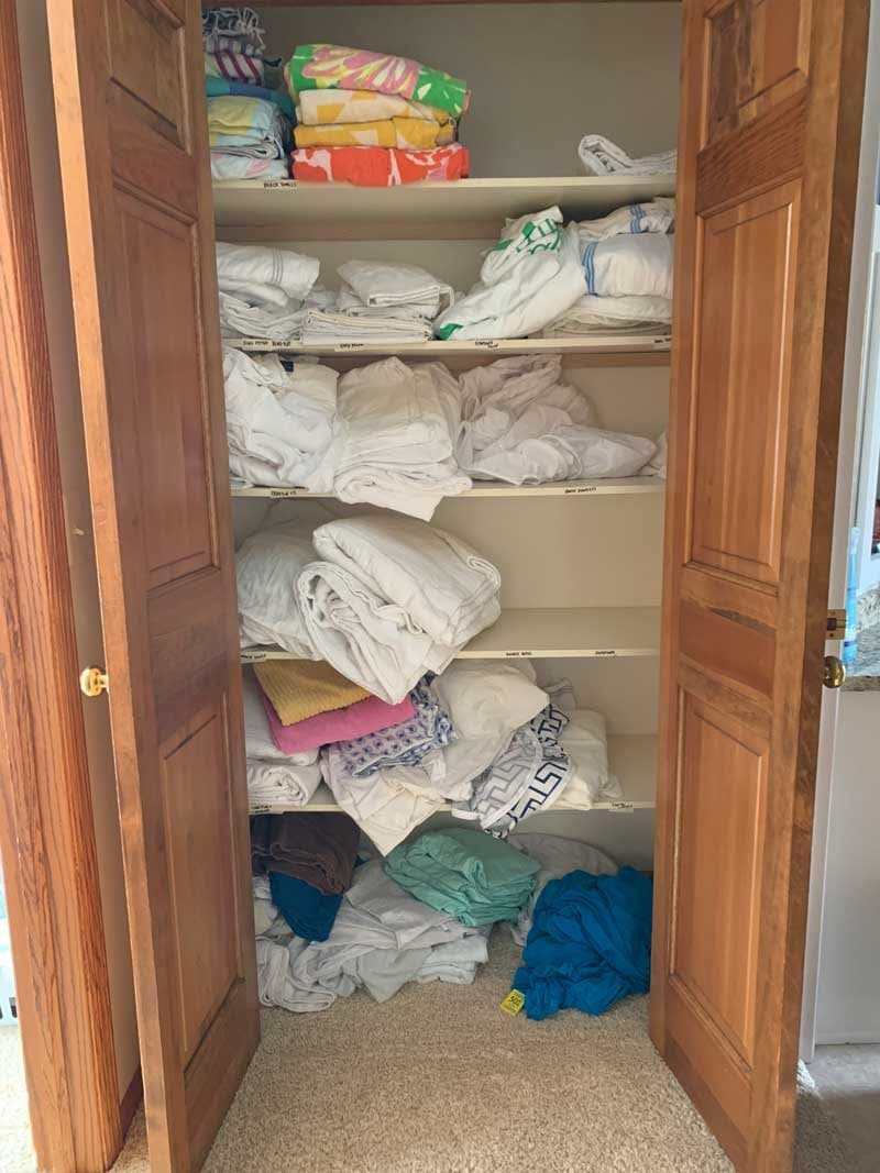messy linen closet before makeover