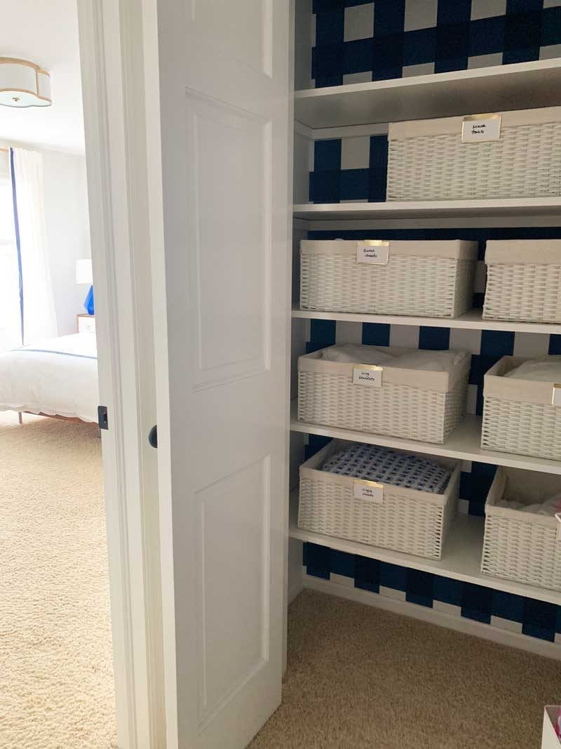 organized linen closet with white baskets
