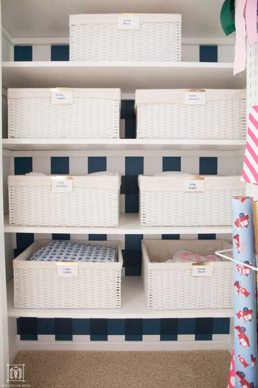 white baskets with bed sheets in a linen closet with blue and white wallpaper