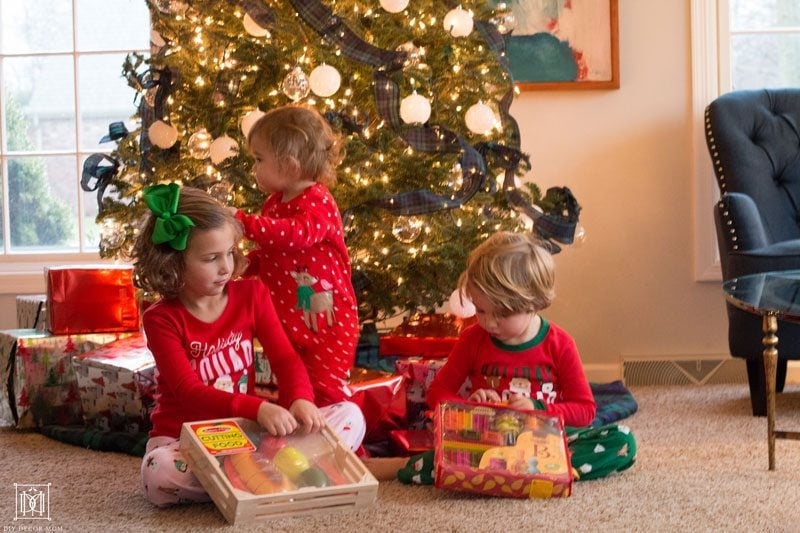 kids opening gifts in front of tree