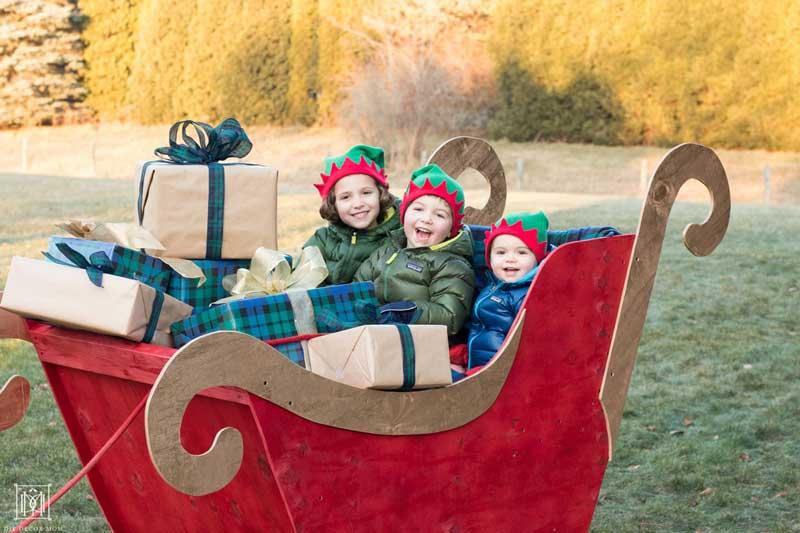 kids sitting in a diy santa sleigh in yard