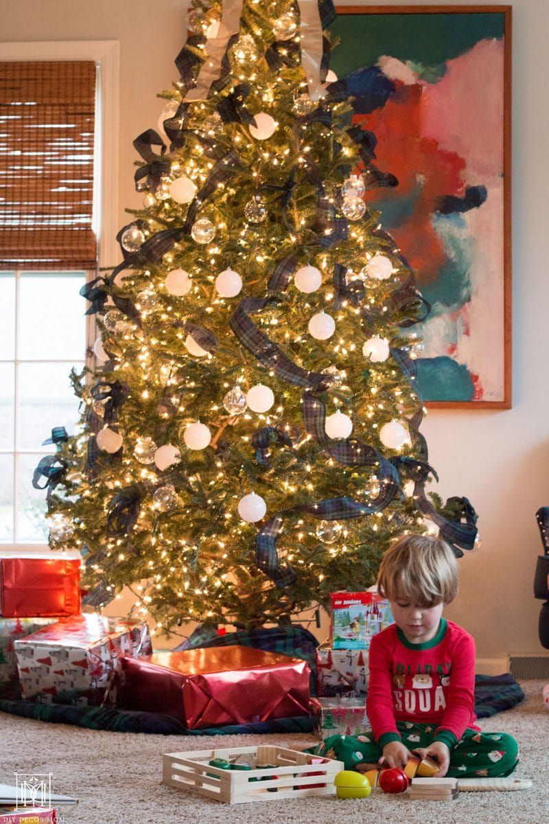 little boy playing with toys from meijer in front of tree