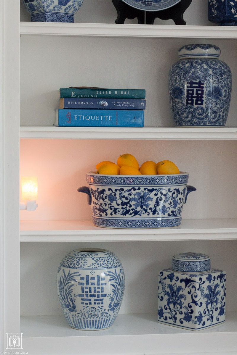 salt lamp plugged into bookshelf with blue and white pottery