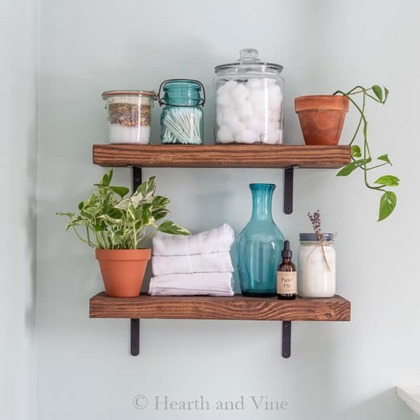 DIY wood shelves with potted plants in bathroom by Hearth and Vine