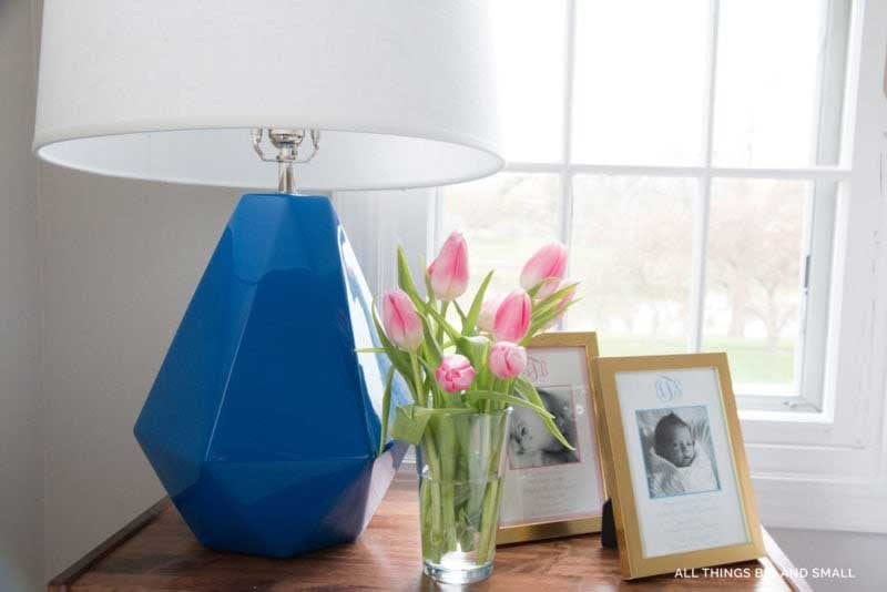 tips for making your bedside table in your bedroom look nice with blue lamp and flowers