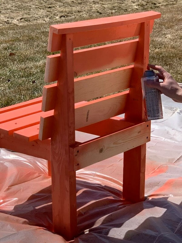 man spray painting diy fire pit bench curved