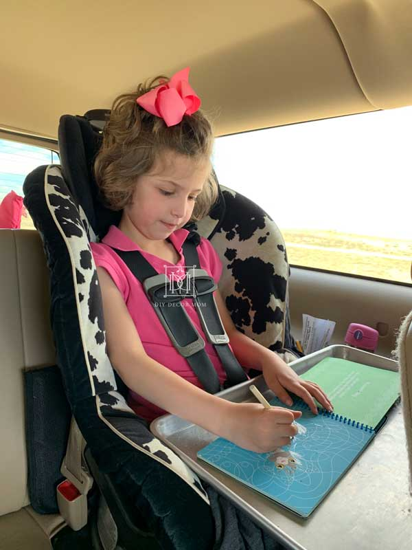 kid in carseat working on road trip activities