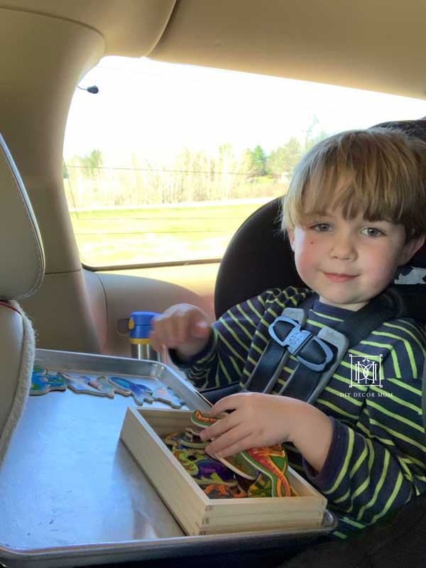 toddler boy playing with magnets on road trip with family