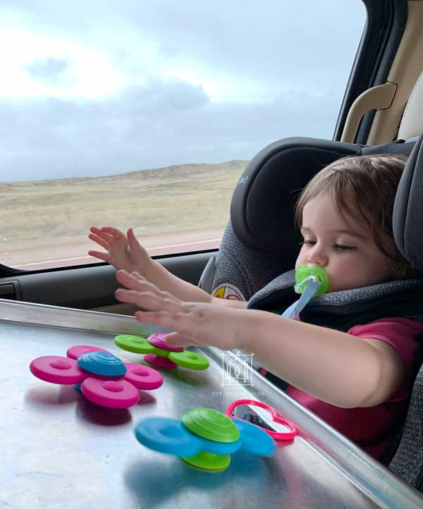 toddler playing with non-electronic road trip activities for kids
