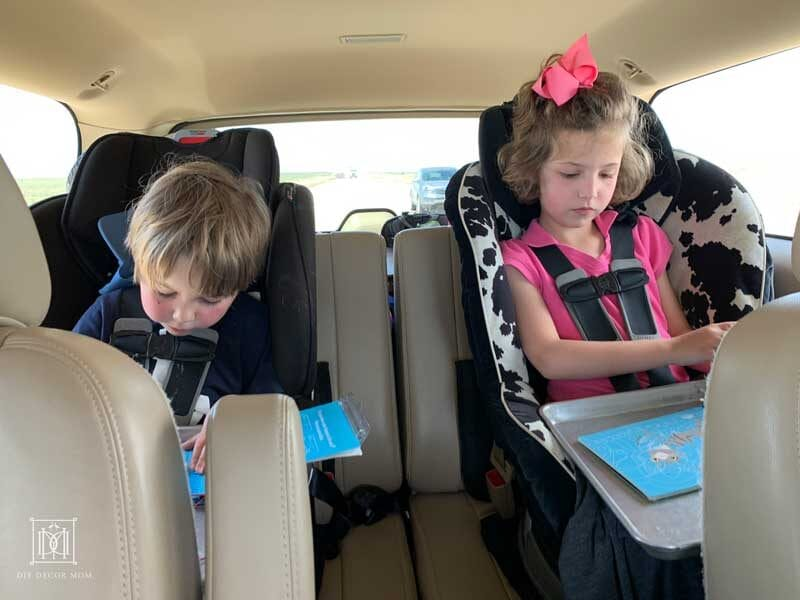 two kids in carseats doing road trip games and activities on family road trip