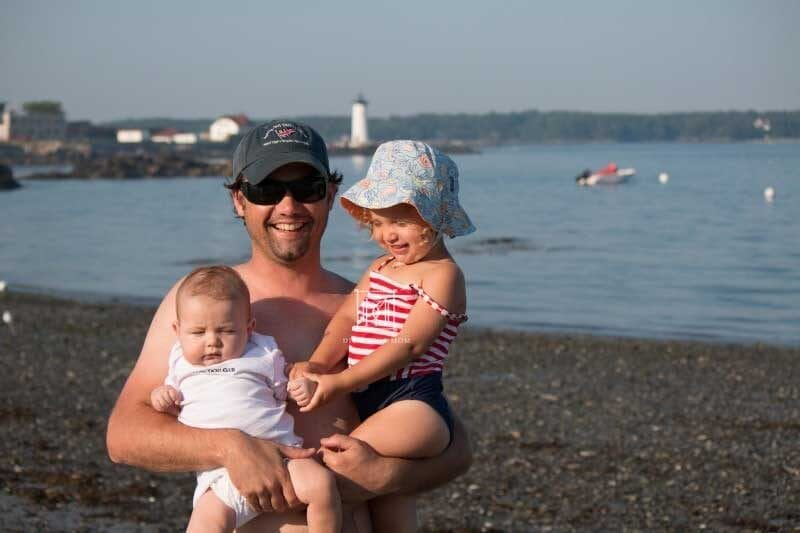 dad holds baby and toddler at beach--tips for helping toddler adjust to new baby