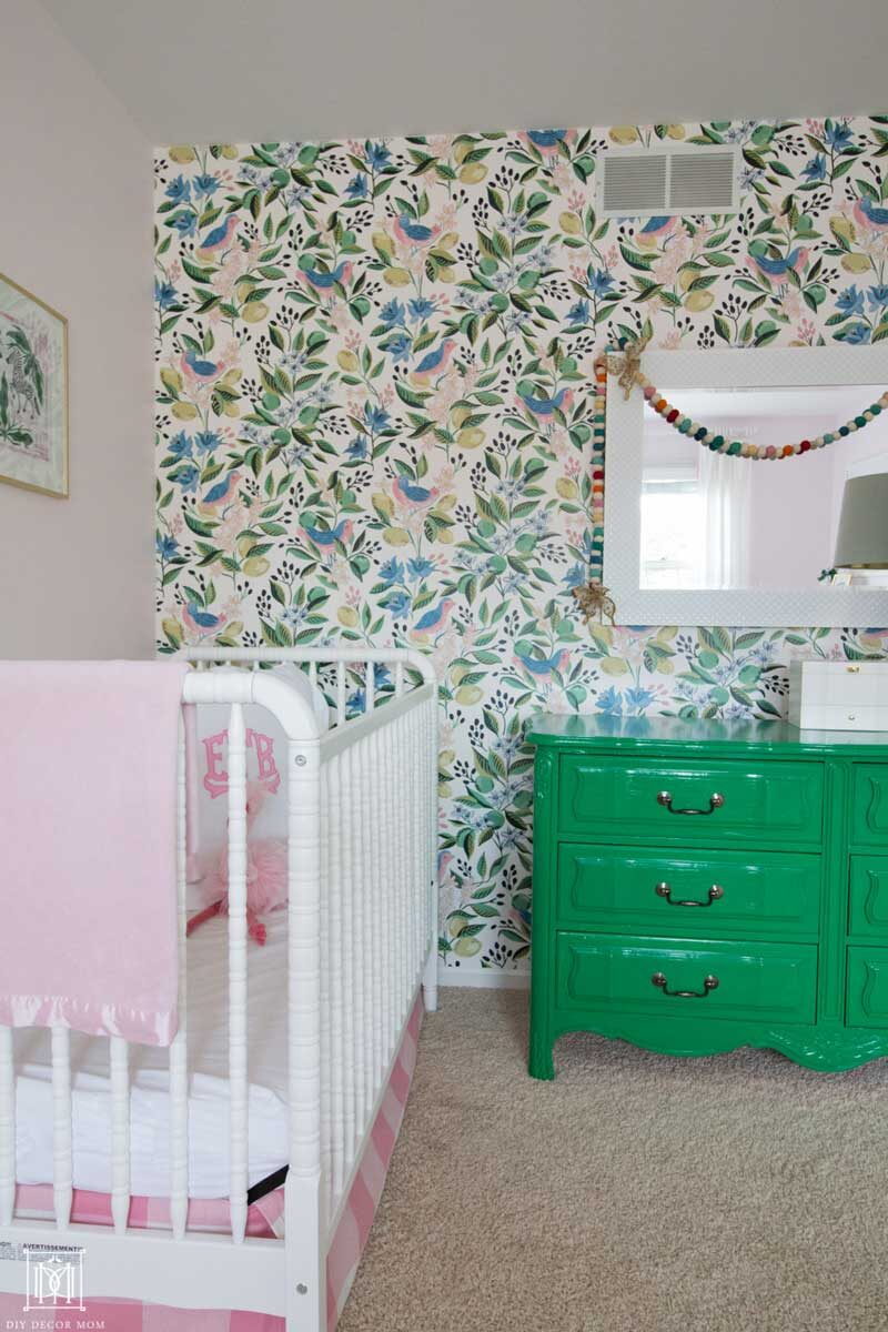 crib with wallpaper accent wall in girls bedroom