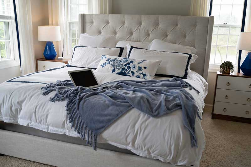 relaxing bedroom ideas- cozy bed with blanket and laptop
