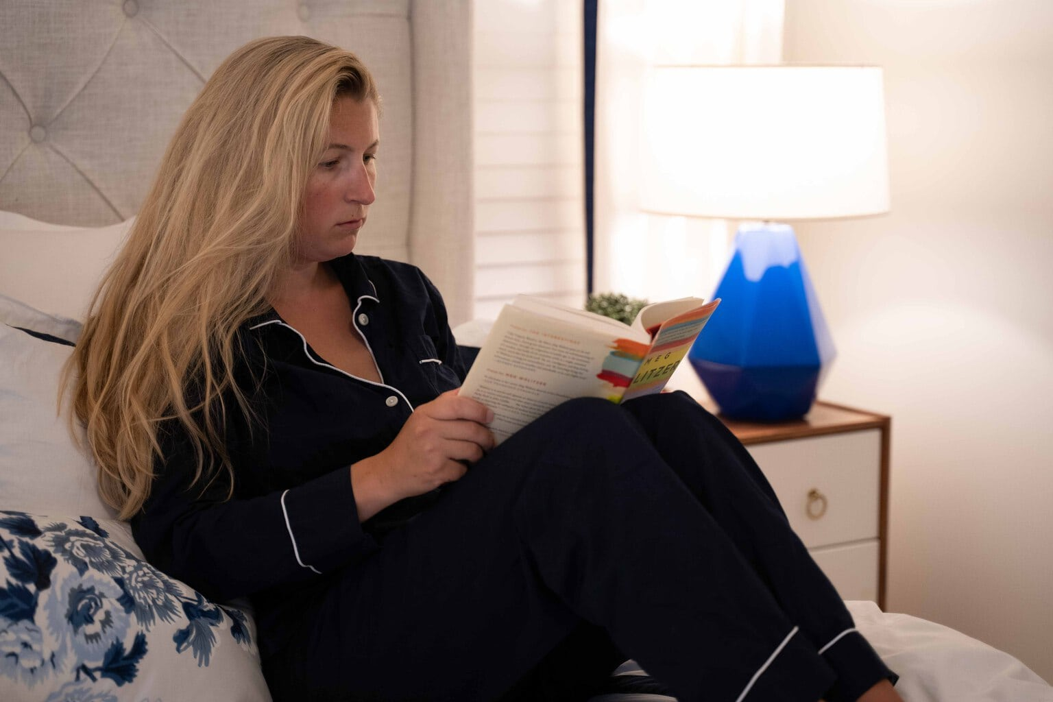 woman relaxing in bed reading a book with ambient lighting