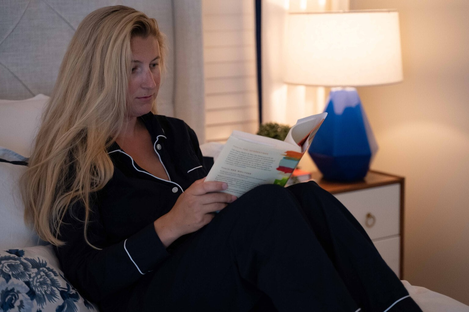 woman reading in comfy cozy relaxing bedroom