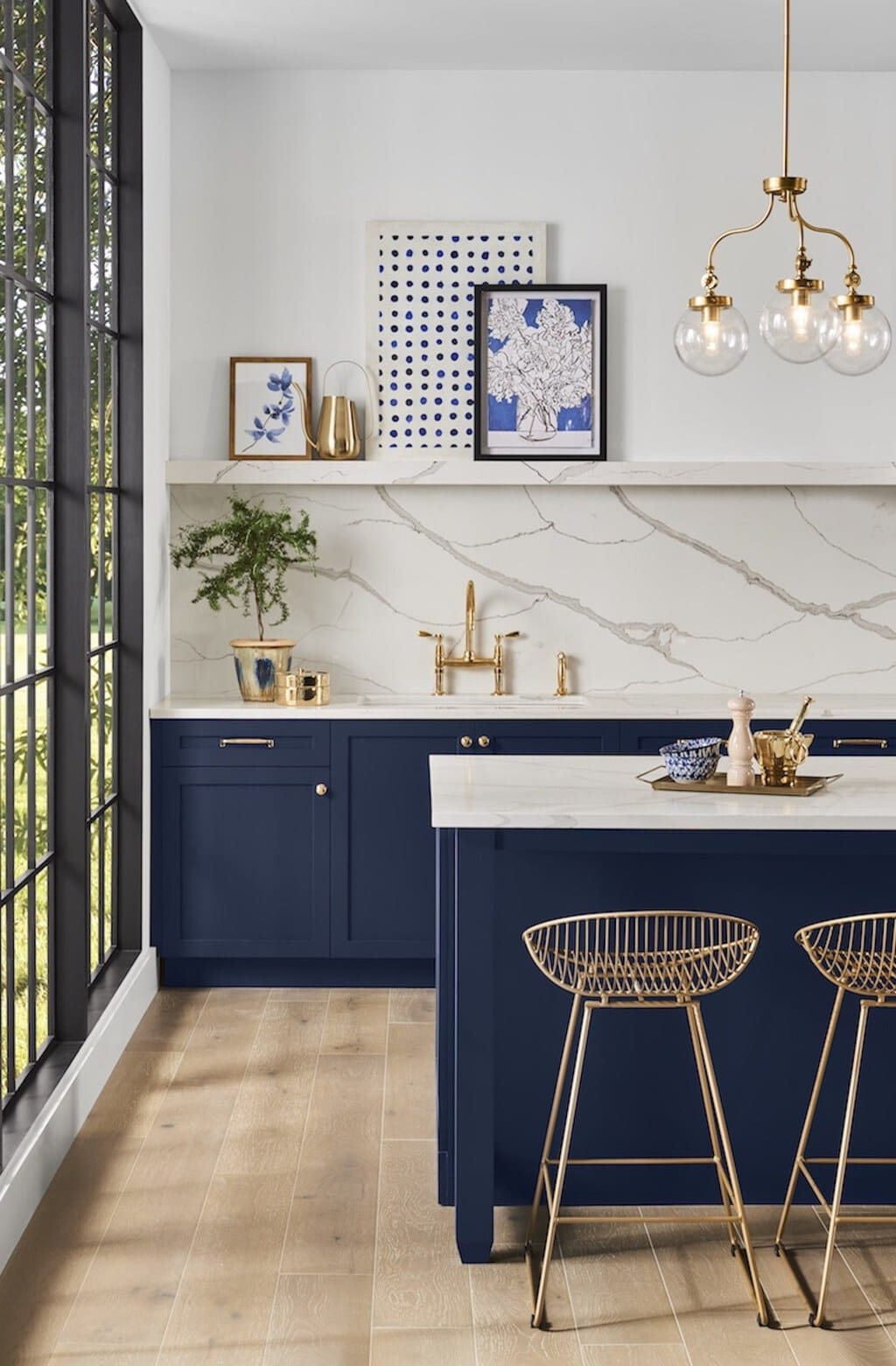 sherwin-williams naval painted kitchen cabinets with marble backsplash and gold accessories and bar stools