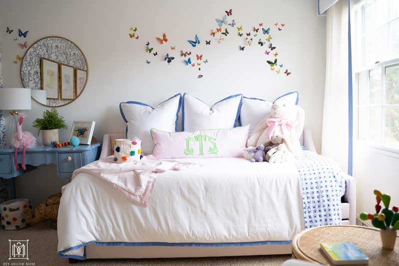 pink upholstered daybed in nursery with white bedding and monogrammed pillows- butterfly artwork wall decor
