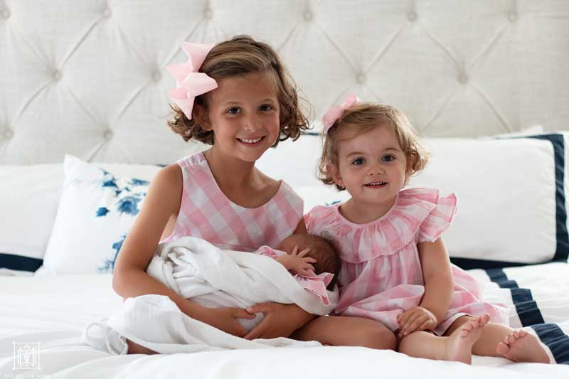 two girls in pink outfits sitting on white bed holding newborn
